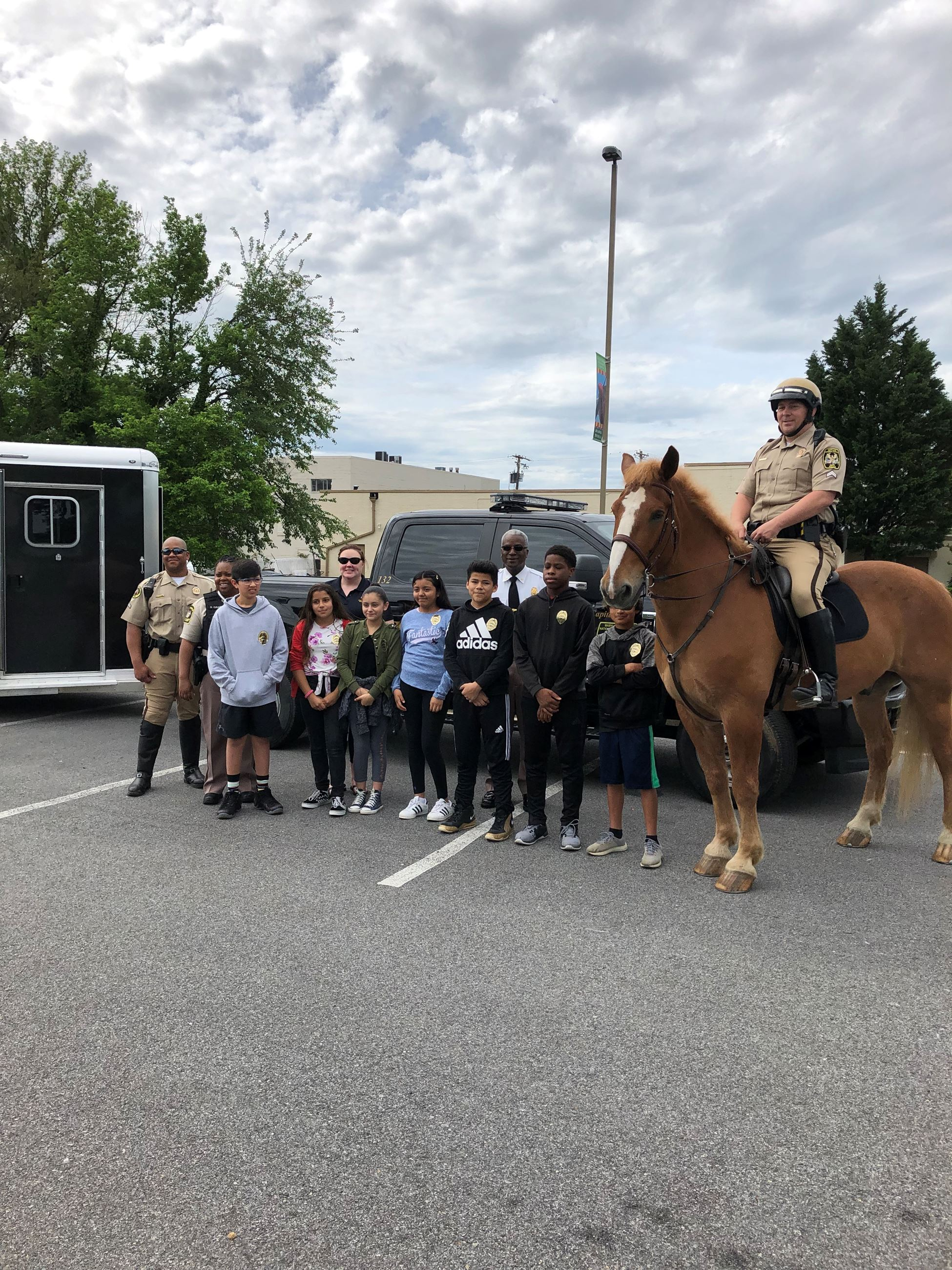 Chief for the Day students stand with mounted police