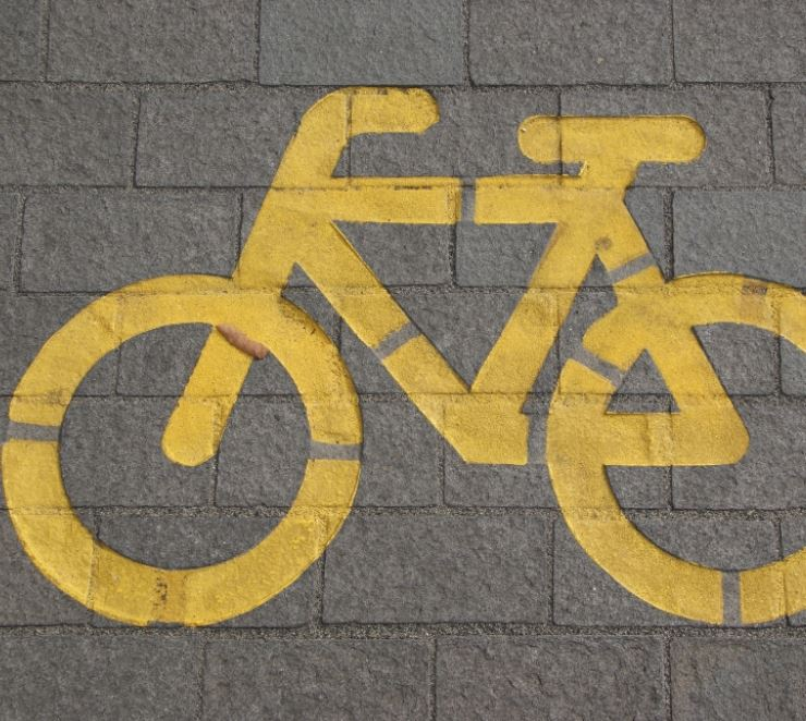yellow chalk outline of a bicycle against a brick background