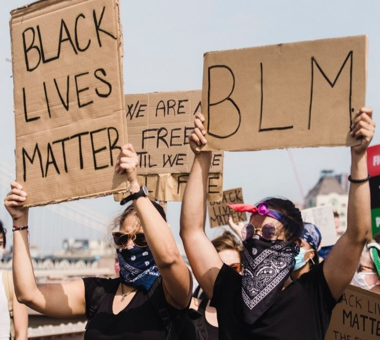 Protesters holding signs that say Black Lives Matter and BLM